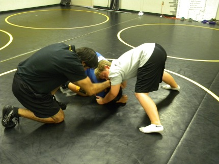 Coach Mestakides helps with a front head lock.